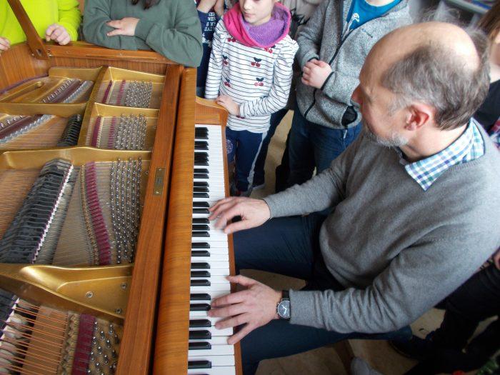 Sven Schnoor erklärt den Grundschülern der 4. Klasse in Waging den Aufbau eines Klaviers