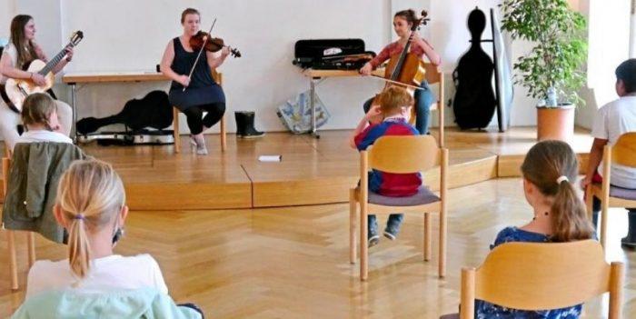 Nicole Pirnbacher (links), Anna Kinschel (Mitte) und Cecilia Clo (rechts) stellen im Alten Rathaus in Laufen die Instrumente Gitarre, Violine und Cello vor.